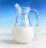 Jug of milk on sky background. Half full pitcher Stock Image