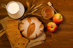 Jug with milk, spikelets, rye bread, honey and apples on a wooden table, top view Royalty Free Stock Image
