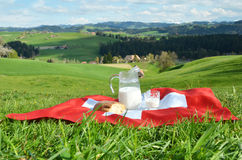 Jug of milk on the Swiss flag stock images