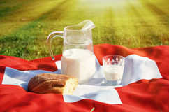 Jug of milk on the Swiss flag Royalty Free Stock Photography