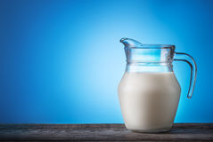 Jug with milk on wooden table Royalty Free Stock Images