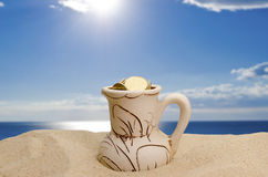 Jug with money on a beach Royalty Free Stock Photo