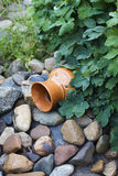Jug old and vintage under green grass on stones Royalty Free Stock Photo