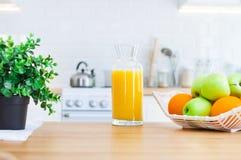 Jug of orange juice and fruit on the kitchen table royalty free stock photo