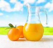 Jug of orange juice on nature background Royalty Free Stock Photography