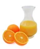 Jug orange juice with oranges on white. A carafe of fresh orange juice with oranges on a white background Royalty Free Stock Photos