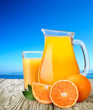 Jug or pitcher with highball of orange juice with oranges Royalty Free Stock Images