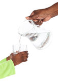 Jug pouring water. Hand of an african adult men is holding a jug of water and pouring it into a clear glass in the hands of a small african child with green Royalty Free Stock Image