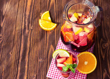 A jug of refreshing sangria with fruits on wooden background Royalty Free Stock Images