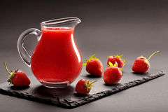 Jug of strawberry juice with space for text Stock Photos