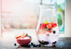 Jug with summer drink with water and berries. Berries lemonade on terrace table over nature background. Stock Images