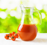 Jug of tomato juice on nature background. Half full pitcher Royalty Free Stock Images