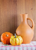 Jug and two pumpkins on the checkered napkin Royalty Free Stock Photography