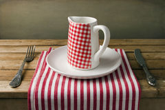 Jug on white plate on wooden table. Royalty Free Stock Images