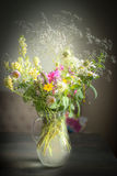 Jug with wild field flowers bunch on rustic table Stock Images