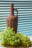 Jug of wine and grapes. Jug of homemade wine and grapes on a tray Stock Photography