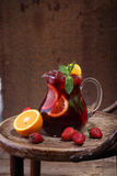 Jug of wine of Sangrija on a wooden table with an orange and a s. Trawberry stock photos