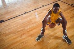 Jugador adolescente pensativo que se sienta en baloncesto Fotos de archivo