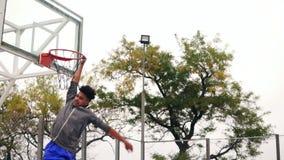 Jugador africano joven que salta para arriba y que golpea un anillo del baloncesto por su mano Tiro a cámara lenta almacen de video