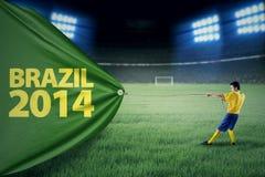 Jugador brasileño que tira de una bandera del campeonato Imagen de archivo libre de regalías