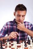 Jugador de ajedrez joven que piensa en su próximo paso Imagen de archivo libre de regalías