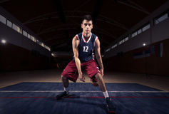 Jugador de básquet, bola entre las piernas Foto de archivo libre de regalías