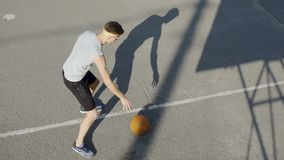 Jugador de básquet caucásico joven que gotea una bola en el estadio, el deporte y la afición almacen de video
