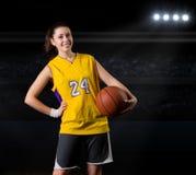 Jugador de básquet de la muchacha en pasillo de deportes imagenes de archivo