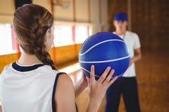 Jugador de básquet de sexo femenino que practica con el coche masculino Foto de archivo libre de regalías