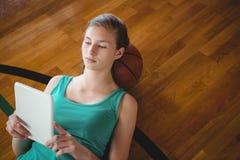 Jugador de básquet de sexo femenino que usa la tableta digital mientras que se relaja ante el tribunal Foto de archivo