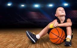 Jugador de básquet del muchacho con una bola que se sienta en el piso en el gimnasio y sueños de grandes victorias fotografía de archivo