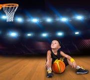Jugador de básquet del muchacho con una bola que se sienta en el piso en el gimnasio y sueños de grandes victorias imagen de archivo libre de regalías