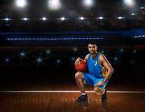 Jugador de básquet en la sentada uniforme del azul en la cancha de básquet imagenes de archivo