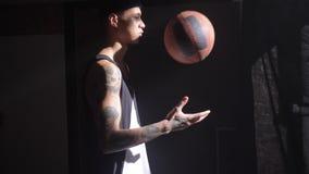 Jugador de básquet hermoso con los tatuajes que juegan con la bola y para el juego que espera para comenzar almacen de video