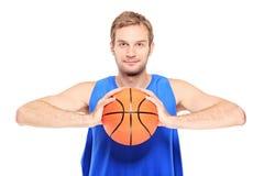 Jugador de básquet joven que presenta con un baloncesto Imagenes de archivo
