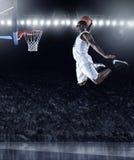 Jugador de básquet que anota una clavada atlética, asombrosa fotografía de archivo