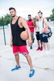 Jugador de básquet que celebra la bola con el equipo multicultural que se coloca detrás imagen de archivo