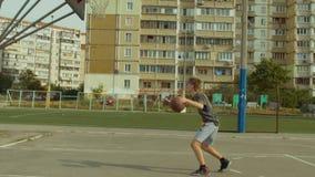Jugador de básquet que gotea la bola entre las piernas almacen de metraje de vídeo