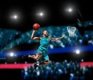 Jugador de básquet que hace clavada en arena del baloncesto Foto de archivo