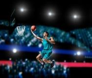 Jugador de básquet que hace clavada en arena del baloncesto Imagen de archivo