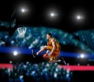 Jugador de básquet que hace clavada en arena del baloncesto Imagenes de archivo