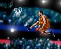 Jugador de básquet que hace clavada en arena del baloncesto fotos de archivo libres de regalías