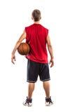 Jugador de básquet que se coloca con la bola de la parte posterior Fotos de archivo libres de regalías
