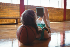 Jugador de básquet que usa la tableta ante el tribunal Imágenes de archivo libres de regalías