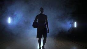 Jugador de básquet de sexo masculino que se mueve en el humo en la cámara que golpea la bola sobre la tierra del entarimado en la almacen de metraje de vídeo
