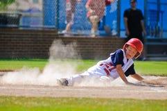 Jugador de béisbol de la liga pequeña que resbala a casa imagen de archivo
