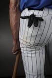 Jugador de béisbol del primer que se inclina en palo Imagen de archivo
