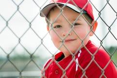 Jugador de béisbol joven que se sienta en cobertizo Fotos de archivo libres de regalías