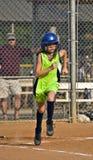 Jugador de beísbol con pelota blanda de la chica joven que se ejecuta a la primera base Imagenes de archivo