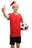 Jugador de fútbol adolescente con el sombrero de la Navidad que hace el pulgar encima de la muestra Imagen de archivo